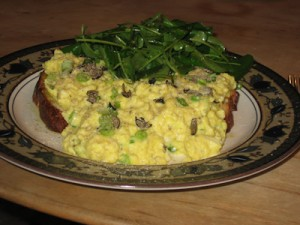 Scrambled eggs on toast with black truffles and arugula salad